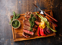 切的Striploin牛排用chimichurri调味汁和菜 免版税库存照片