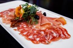 切盛肉盘-意大、bresaola、pancetta、蒜味咸腊肠和巴马干酪的肉 免版税库存照片