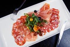 切盛肉盘-意大、bresaola、pancetta、蒜味咸腊肠和巴马干酪的肉 免版税库存图片