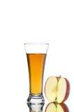 切红色苹果在白色新鲜的汁液隔绝的果子和杯 免版税库存照片
