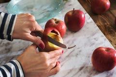 切红色苹果的妇女 步做烹饪苹果蛋糕 库存图片