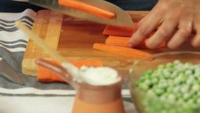 切红萝卜和在家烹调健康食品的妇女 影视素材