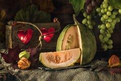 切绿色南瓜在万圣夜反对美好的葡萄背景  仍然1寿命 免版税库存照片