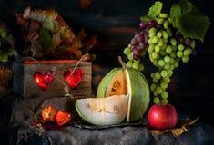 切绿色南瓜在万圣夜反对美好的葡萄背景  仍然1寿命 免版税库存图片