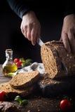 切自创multigrain面包的女性手 库存图片