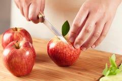 切苹果的妇女 免版税库存照片