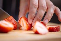 切草莓的刀子 免版税图库摄影