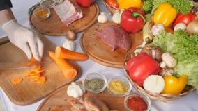 切菜,反抗在红萝卜手套的手特写镜头,餐馆厨房,静物画背景 影视素材