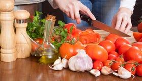 切蕃茄的女性手 免版税库存图片
