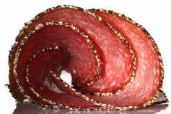 切被扭转的德国胡椒蒜味咸腊肠香肠 库存图片