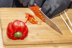 切辣椒粉厨师 烹调健康食品饮食健康食品 在木桌,在黑橡胶glo的厨师手上的木切板 库存照片
