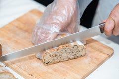 切面包在厨房里,刀子的厨师 免版税图库摄影