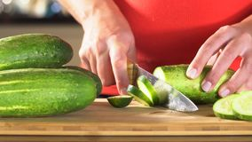 切黄瓜的妇女 女性手削减了绿色黄瓜圆环 大刀子 在厨房里 木板 关心家事妇女 新鲜的c 股票录像