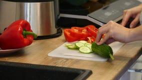 切黄瓜的妇女 女性手削减了绿色黄瓜圆环 大刀子 在厨房里 木板 关心家事 影视素材