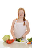 切黄瓜的小女孩 免版税图库摄影