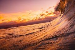 划分在日落或日出时间的海浪 挥动和与温暖的日落或日出颜色 免版税库存图片