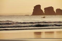 划独木舟的人划船和渔剪影在deux jumeaux的大西洋在日出 免版税库存照片