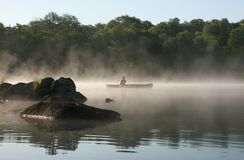 划独木舟的人有薄雾haliburton的湖 免版税库存照片