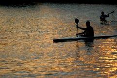 划独木舟的人湖用浆划 库存图片