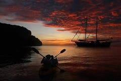 划皮船回到有红色天空太阳的游艇的母亲和女儿 免版税库存照片