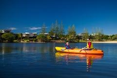 划皮船在一个小湖的母亲和儿子 免版税库存图片