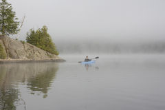 划皮船在一个有薄雾的湖 库存照片