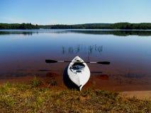 划皮船在一个镇静湖的岸 库存图片