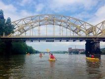 划皮船在一条河的一座桥梁下在匹兹堡 免版税库存照片