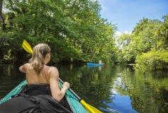 划皮船在一条美丽的热带密林河下的妇女 免版税图库摄影