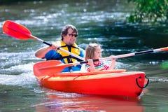 划皮船在夏天的父亲和孩子 免版税库存图片
