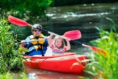 划皮船在夏天的父亲和孩子 图库摄影