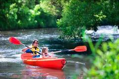 划皮船在夏天的父亲和孩子 免版税图库摄影
