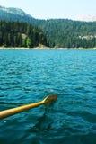 划皮船在山湖,桨在水中 免版税库存图片