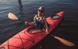 划皮船在日落的妇女 库存图片