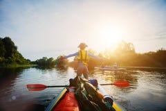 划皮船在日落的河的愉快的男孩在暑假时 免版税库存照片