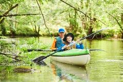 划皮船在森林家庭的河在独木舟 活跃休闲和假期 免版税库存照片