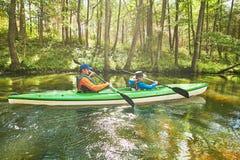 划皮船在森林家庭的河在独木舟 活跃休闲和假期 免版税图库摄影