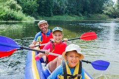 划皮船在河的家庭 免版税库存图片