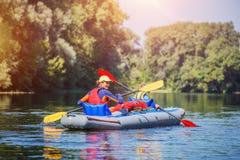 划皮船在河的愉快的女孩在一个晴天在暑假时 免版税库存图片
