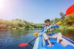 划皮船在河的愉快的男孩在一个晴天在暑假时 免版税库存图片