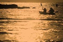 划皮船在海的人们 免版税库存图片