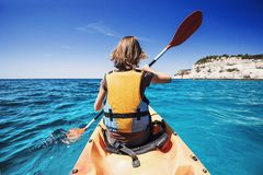 划皮船在海的年轻女人 活跃生活方式和旅行概念 图库摄影