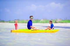 年轻划皮船在海的父亲和两个小孩 免版税图库摄影