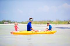 年轻划皮船在海的父亲和两个小孩 免版税库存图片