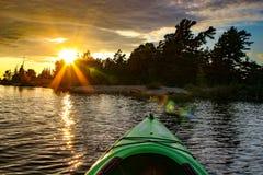 划皮船在湖在火热的日落 Muskoka地区安大略 免版税库存图片