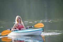 划皮船在湖的美丽的年轻白肤金发的妇女 免版税图库摄影