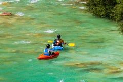 划皮船在绿宝石,绿松石山河的夫妇 免版税库存图片