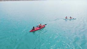 划皮船在蓝色海,极端,活跃旅行 皮船的人们在蓝色海游泳 摄制在上面附近,与 影视素材
