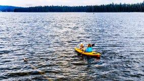 划皮船在Lac Le Jeune湖在坎卢普斯附近,不列颠哥伦比亚省,加拿大 免版税图库摄影