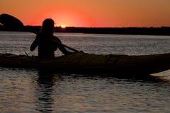 划皮船妇女的剪影  免版税库存图片